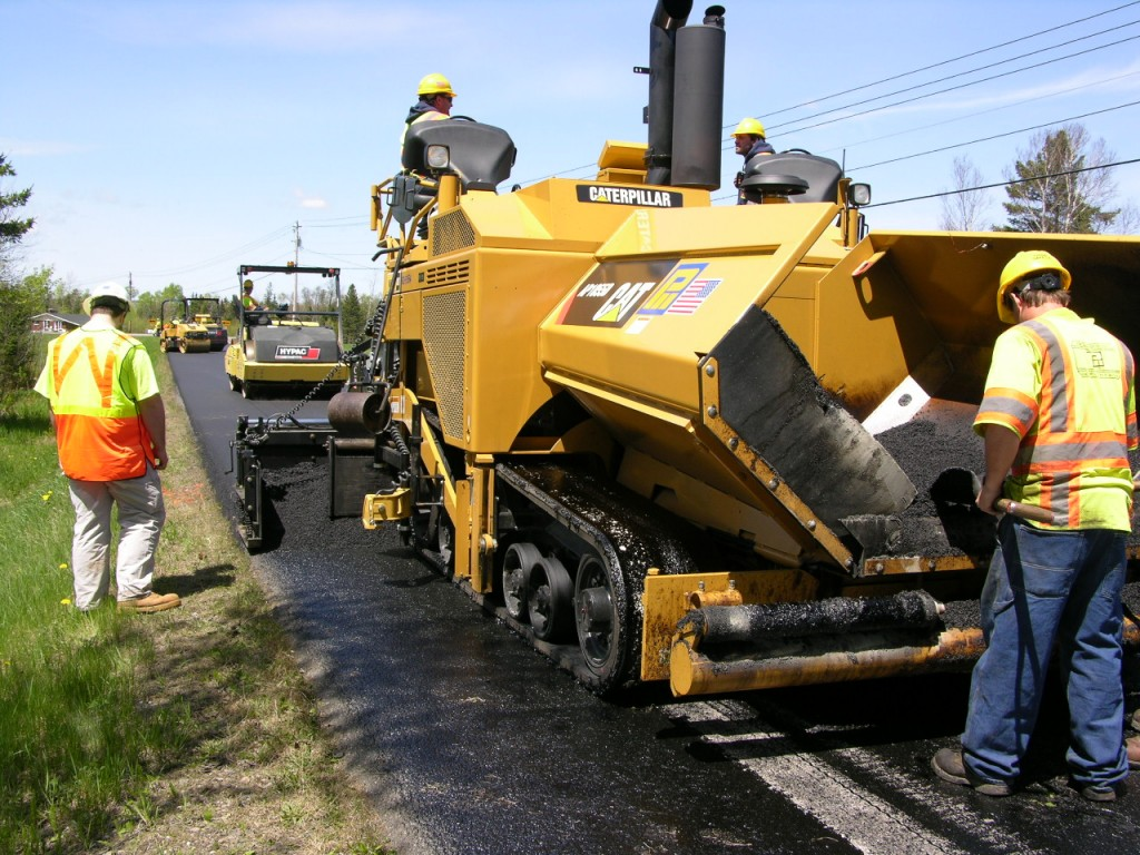 CAT paver awaits a truckload of mix as HYPAC breakdown roller, CAT secondary roller and HYPAC finish roller compact the thin layer.