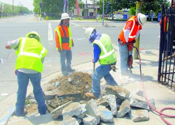 Workers break up sidewalk to make way for installation of crosswalk ramps.