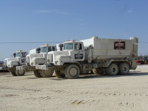 Three of Mt. Carmel Stabilization Group Inc.'s custom built spreader trucks. These Mack trucks are all wheel drive trucks that are designed to get through terrible soil conditions, maintain accurate spread rates and minimize fugitive dust during spreading.