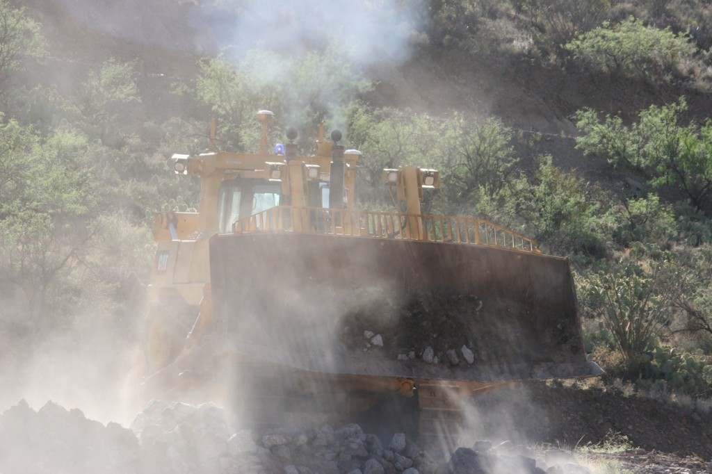 The operator is standing down at the bottom of the bench, well away from the dozer.