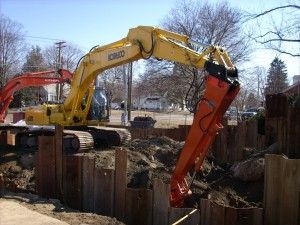 Petroleum Services (PSI) Kobelco SK350 is seen here excavating the soil from within the cofferdam and digging to a level about 12 feet below grade. When this level is attained, AMCO will return and install the lower wale systems. These will brace the lower sections of the sheet piles. The pictures show how the Kobelco was modified to provide a 45-foot reach. The original bucket was removed and an attachment was added to the stick. This attachment allows for the quick connection of the extension. It is better than the usual long stick in that the digging capacity is not reduced very much and it allows for better access in tight areas.
