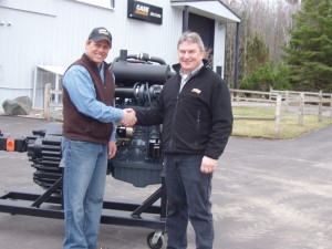 Jon Sowl [left], instructor at Northeast Wisconsin Technical College, accepts donation of Case engine from Russ Wadzinski, general manager of Case Customer Center, Tomahawk, Wis.)